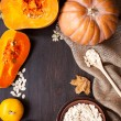 Pumpkins and a bowl with toasted pumpkin seeds, wooden spoon — Stock Photo #58595969