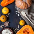 Pumpkins and a bowl with toasted pumpkin seeds, wooden spoon — Stock Photo #59299939