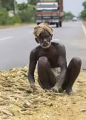 Old dark-skinned farmer works his mellet on public road. — Stock Photo