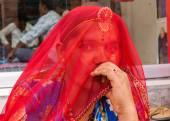 Woman hides her face with red veil. — Stock Photo