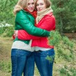 Mother and daughter standing next to Christmas trees — Stock Photo #54836141