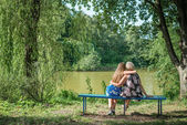 Two women of different generations sitting on a bench near a pond in the summer. Mother and daughter hugging. Grandmother and granddaughter. — Stock Photo