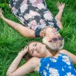 Two women of different generations lie on the grass. Mother and daughter. Grandmother and granddaughter — Stock Photo #66127757