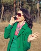 Brunette woman talking on a smartphone in nature — Stock Photo