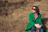 Woman sitting on the hay in a green coat — Stock Photo