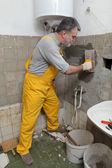 Home renovation, mason fixing wall — Stock Photo
