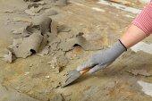 Pracovník pomocí špachtle na čištění podlahy — Stock fotografie