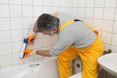 Worker caulking bath tube and tiles — Stock Photo