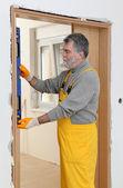 Builder measure verticality of door with level tool — Stock Photo
