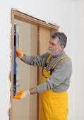 Builder measure verticality of door with level tool — Stock Photo