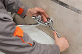 Plumber fixing faucet in a bathroom — Stock Photo