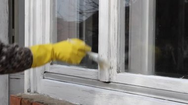 Home renovation, worker painting old wooden window, hand in glove and paintbrush — Stock Video