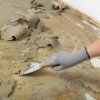Worker using putty knife for cleaning floor — Stock Photo #69820391
