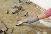 Worker using putty knife for cleaning floor — Stock Photo
