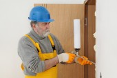Worker installing wooden door, using polyurethane foam — Stock Photo