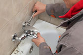 Plumber works in a bathroom — Stock Photo