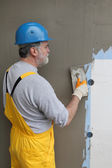 Wall insulation, spreading mortar over mesh and styrofoam — Stock Photo
