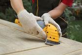 Home renovation, worker sanding wooden door — Stock Photo