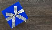 Großen blauen Geschenkbox mit grauer Bogen auf hölzernen Hintergrund — Stockfoto