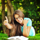 Happy smiling girl in glasses lying in the park near a book and  — Foto Stock