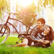 Happy smiling young couple lying in a park near a vintage bike — Stock Photo #52448939