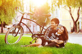 Happy smiling young couple lying in a park near a vintage bike  — 图库照片