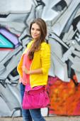 Beautiful stylish fashion woman at graffiti wall in city — ストック写真
