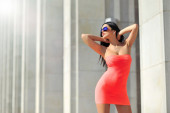 Beautiful brunette young woman in red dress posing outdoor   — ストック写真