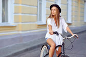 Young lady on a vintage bicycle looking at copyspace — Stock Photo