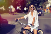 Attractive young woman on a bicycle in a city — Stock Photo