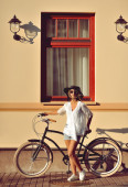 Beautiful blonde standing near her old bicycle. Outdoor fashion — Stock Photo
