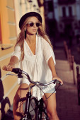 Young sensual female on a vintage bike in an old town — Stock Photo