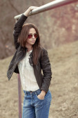 Young sexy brunette woman in jeans, jacket and sunglasses posing — Stock Photo