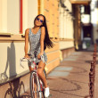 Outdoor fashion portrait of a beautiful brunette with bike — Stock Photo #54094039