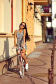 Outdoor fashion portrait of a beautiful brunette with bike — Stock Photo