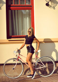 Outdoor fashion portrait of a beautiful blonde with bike — Stock Photo