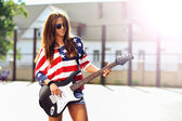 Young beautiful girl with electric guitar. Outdoor fashion portr — Stock Photo