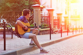 Young hipster man sitting during sunshine with acoustic guitar w — Stock Photo