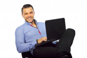 Happy smiling young man sitting at studio with laptop computer i — Stockfoto