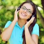 Beautiful young woman with headphones outdoors. Enjoying music — Stock Photo #58532141