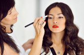 Young beautiful asian woman applying make-up by make-up artist — Stock Photo