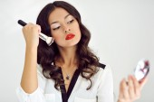 Makeup applying. Beautiful girl with cosmetic powder brush — Stock Photo