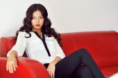 Moda ragazza seduta su un divano rosso a casa — Foto Stock