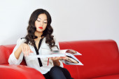 Woman sitting on a sofa and reading magazine  — Stock Photo