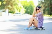 Hermosa y moda joven posando con una patineta — Foto de Stock