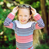 Happy smiling little girl putting off glasses — Stock Photo