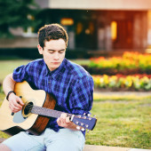 Young hipster man playing guitar in a park  — Stock fotografie