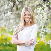 Beautiful girl in blooming tree in spring — Photo