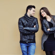 Flirting young couple standing near a wall and looking to each o — Stock Photo #62860399