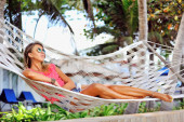 Woman is resting in the hammock under the palms on the tropical — Stock Photo